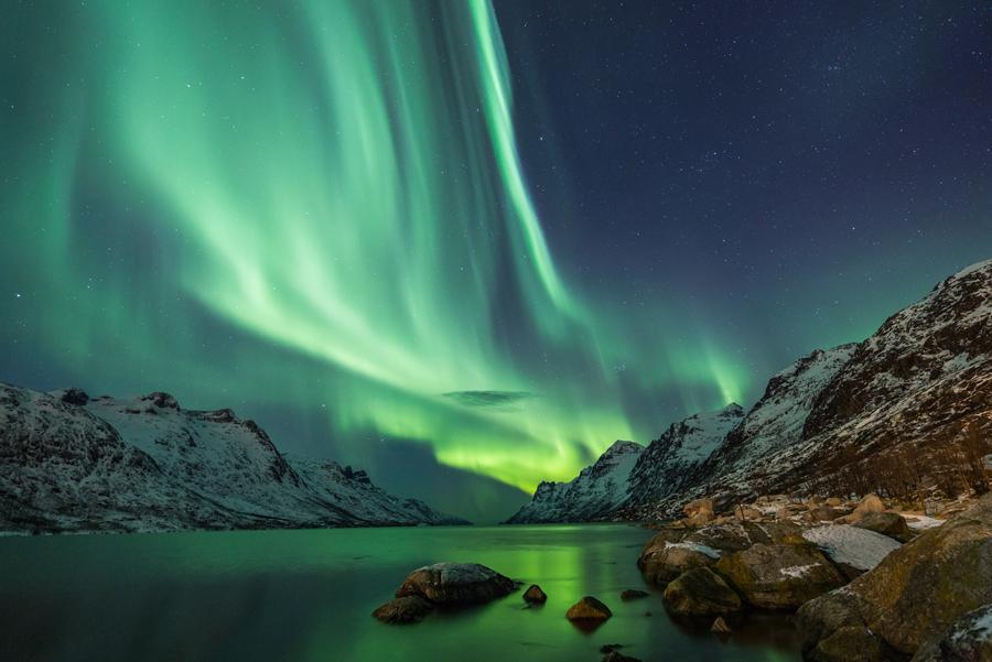 Aurora boreal sobre un lago entre montañas en Islandia.