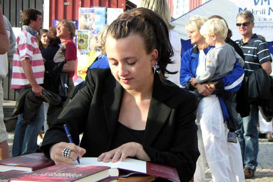 Camila firmando ejemplares de sus libros.