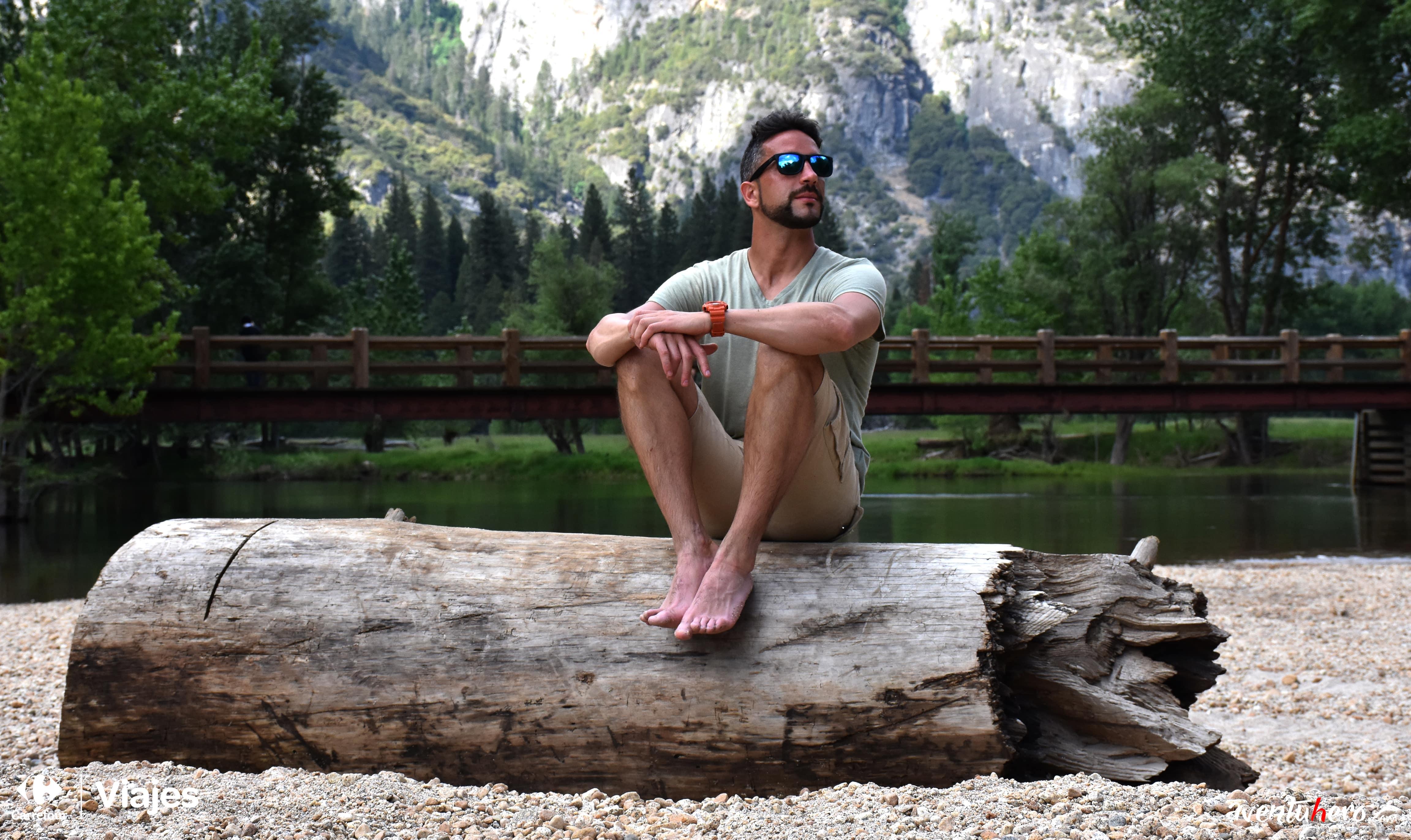 Aventuhero sentado en un tronco en Yosemite