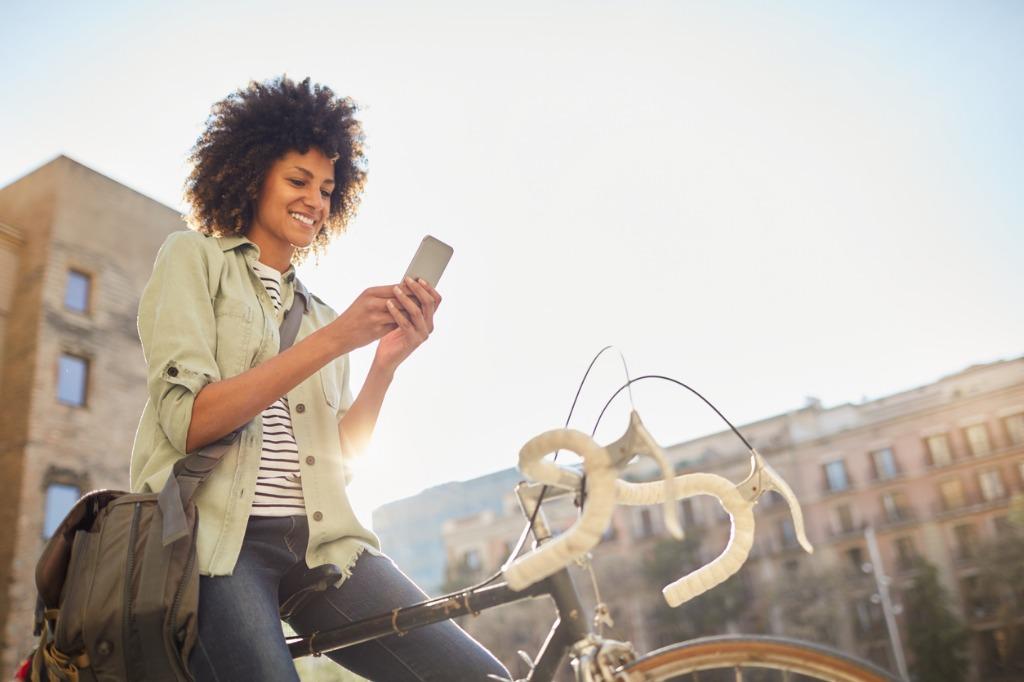Chica en bicicleta consultado el móvil