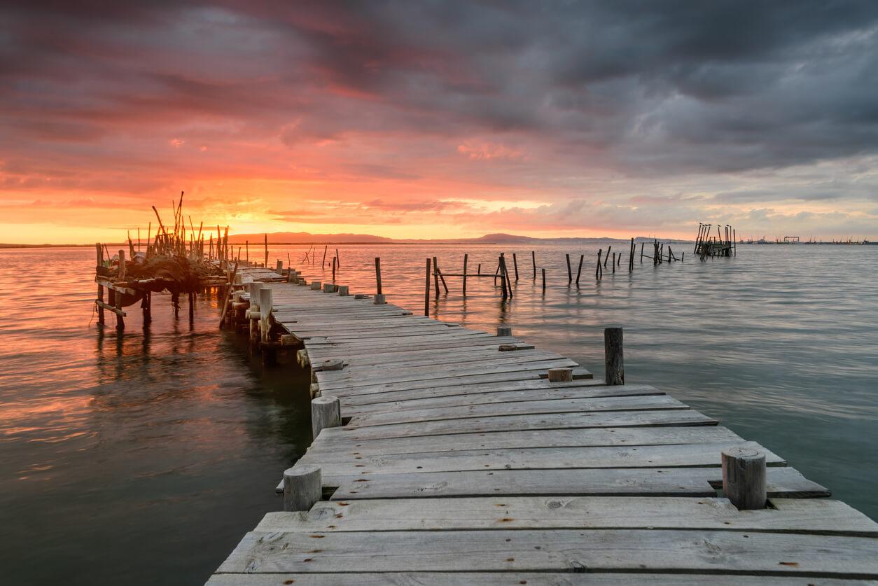 Puesta de sol paisaje de barcos de pesca artesanal en el viejo muelle de Troia