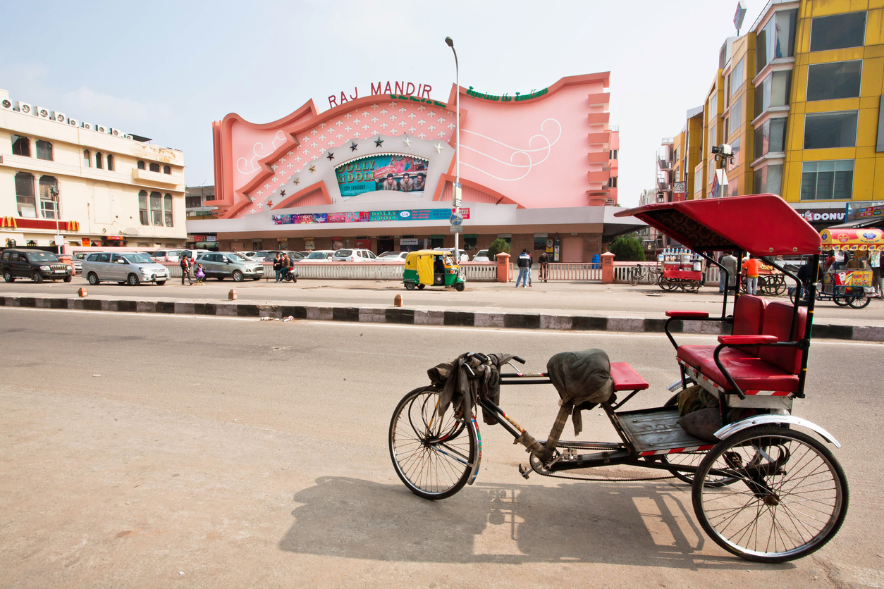 Jaipur, India - January 25, 2015: Traditional indian trishaw transport stands past the famous Raj Mandir movie theater on January 25, 2015. Raj Mandir Cinema was designed in Art Moderne style in 1976