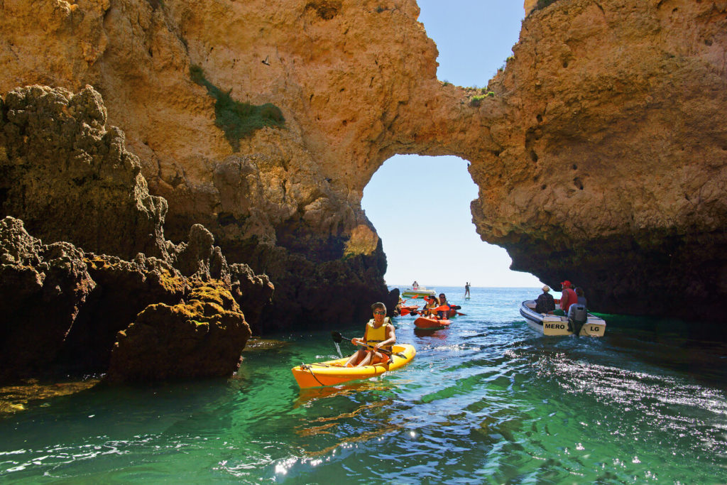Kayakistas y un barco de tour en una de las muchas grutas, Ponta da Piedade, el Algarve, Portugal
