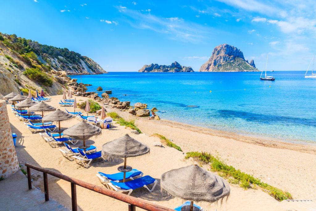 Vista de Cala d ' Hort playa con tumbonas y sombrillas y aguas del hermoso mar azul, isla de Ibiza, España