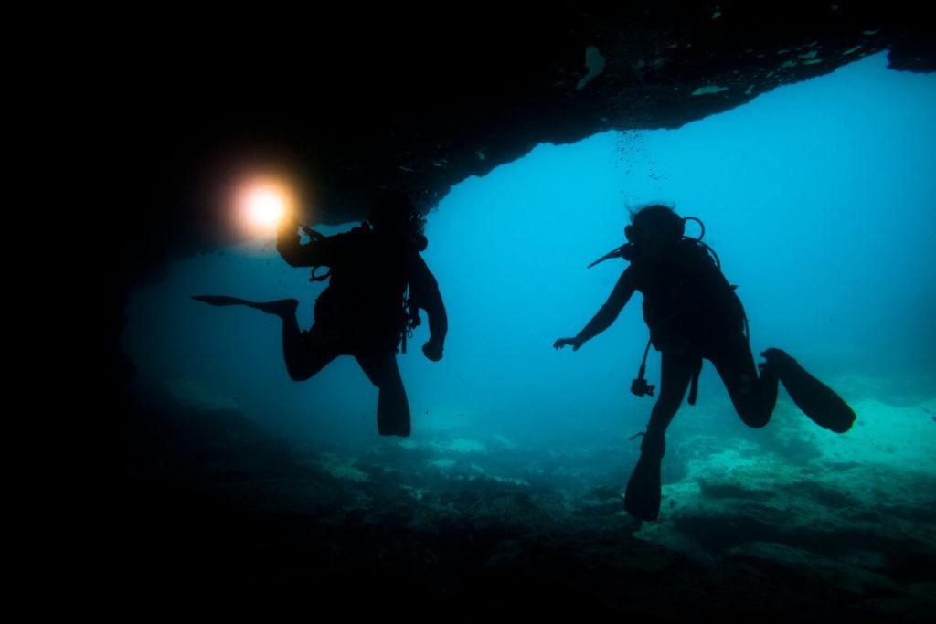 Buzos de la silueta en una cueva