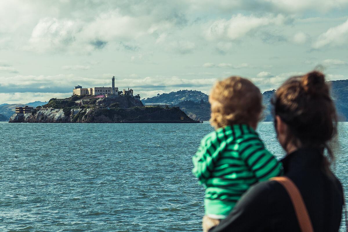 madre y su hijo miran al horizonte donde se ve la prisión de Alcatraz